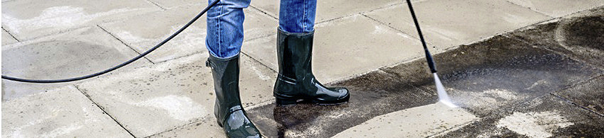 Bottom half of person wearing blackrubber boots holding pressurer washer wand