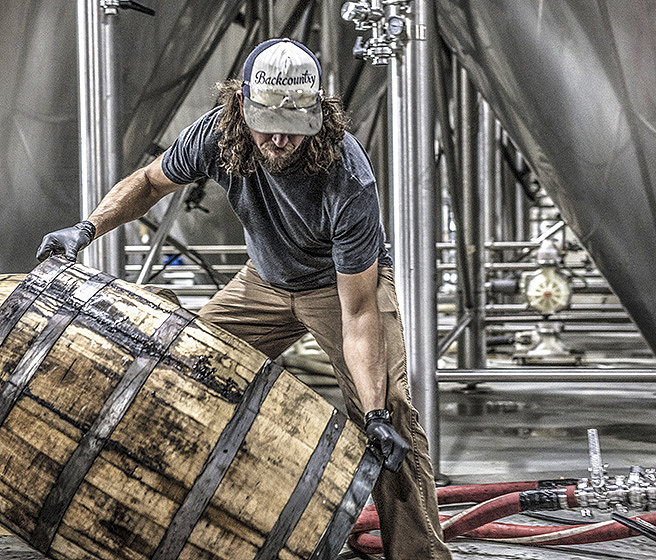 Food and beverage worker moving a barrel